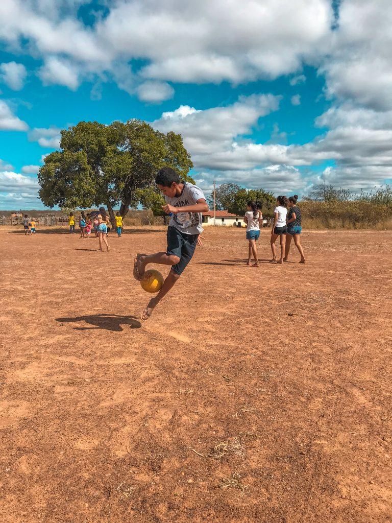 Menino jogando bola no sertão