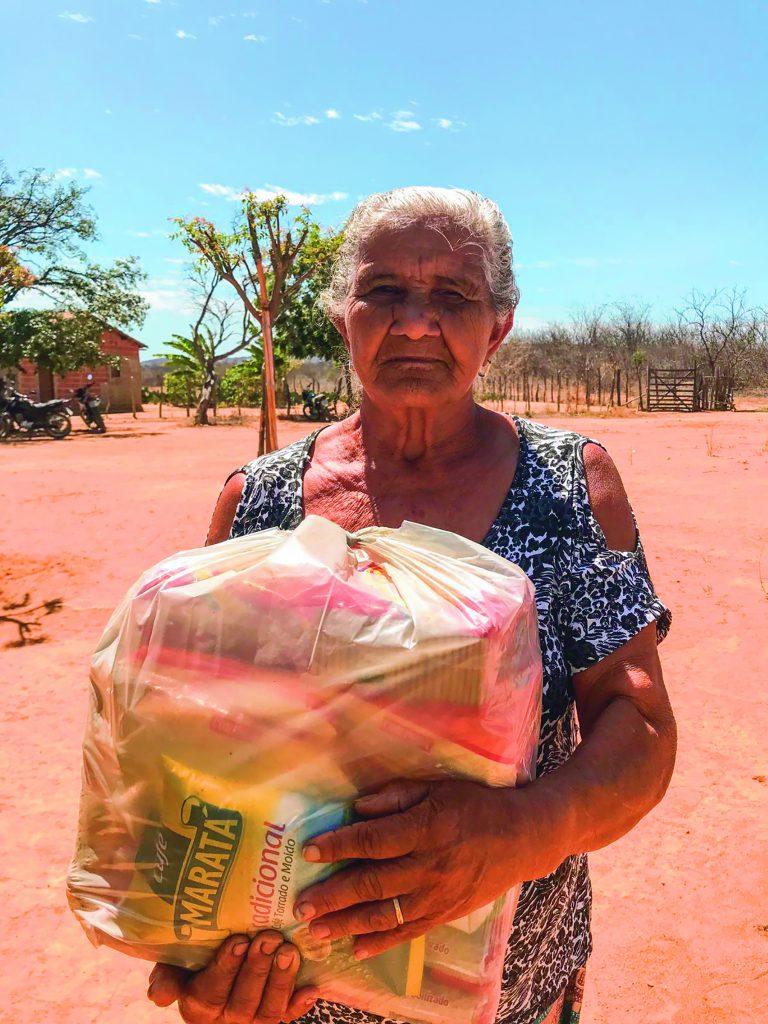 Senhora segurando cesta básica